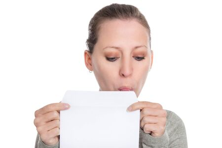 young woman holding and licking a white envelope, isolated on white