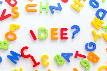strategically: lots of colorful letters on a table, german word in the center, idee which means idea