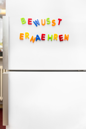 consciously: colorful magnet letters with german text bewusst ernaehren, wich means healthy nutrition or alimentation