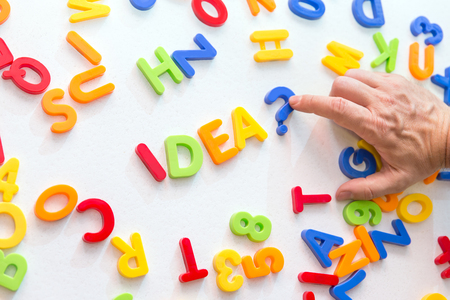 strategically: lots of colorful letters on a table, man forming the word idea, concept future and knowledge Stock Photo
