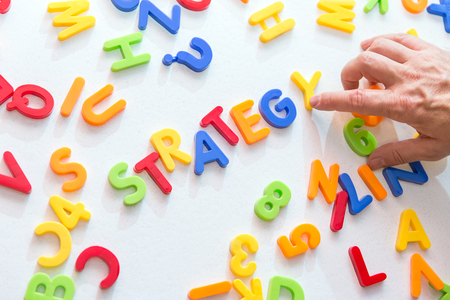 strategically: lots of colorful letters, hand building word strategy, concept business and planning Stock Photo