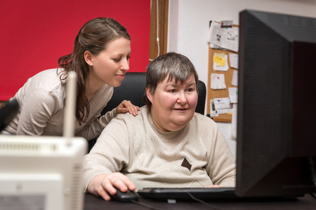caregiver and mentally disabled woman learning at the computer, special education