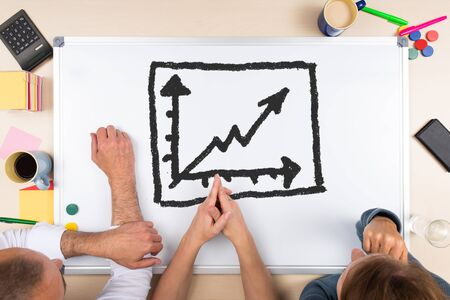 business money: whiteboard with drawing chart, three persons