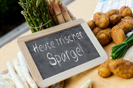 sundry: sundry Asparagus with blackboard and german words heute frischer spargel, means today fresh asparagus