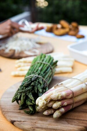 white and green asparagus on a table with new potatoes, woman is peeling the asparagus