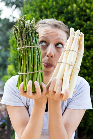 funny woman is holding sundry asparagus in front of her face Stock Photo