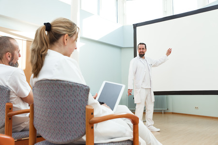 male doctor is doing a lecture in front of other medicine workers Banco de Imagens