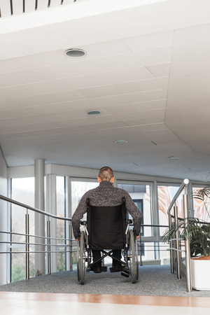 regimen: man sitting in a wheelchair, backview in a hospital