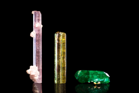 rubellite: Rubellite, green and yellow Tourmaline, group of three mineral stones, black background Stock Photo