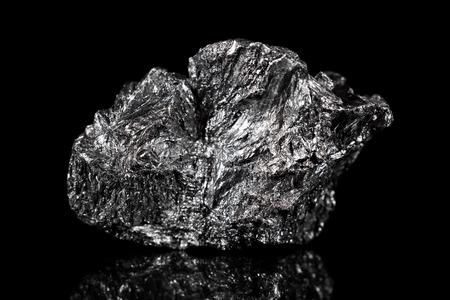 Ruwe minerale steen van grafiet, zwarte specimen koolstof, zwarte achtergrond Stockfoto