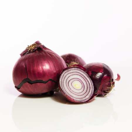 unpeeled: red onions, unpeeled and sliced in front of white