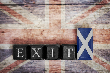 scottish parliament: parts of a keyboard with flag of scotland and word exit, in front of uk flag, concept referendum and independence