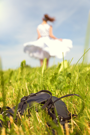 rock n: Woman with a white petticoat dress is dancing on the meadow, shoes in the front Stock Photo