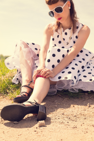 beautiful Pinup Girl with dotted petticoat dress waiting on the wayside