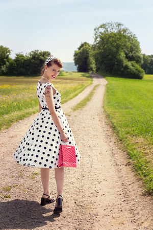 Pinup Girl with a little red shopping bag is walking on a path in the nature