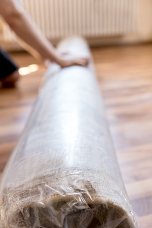 New packed and rolled carpet on the floor, plastic packaging