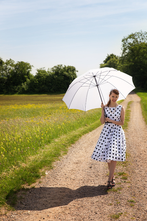 sunshade: Rocknroll Girl with a petticoat dress and a sunshade walking on a path in the sunny nature