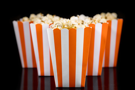 orange striped box with popcorn, black background, concept snack for a Party