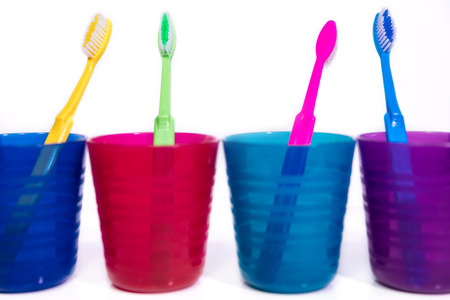 four colorful cups with toothbrushes, white background, concept dental care and hygienic Stock Photo - 78085974