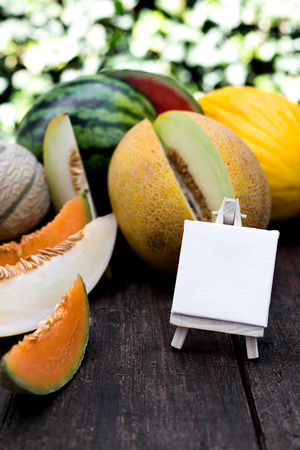 various delicious melons and slices of melons with empty sign