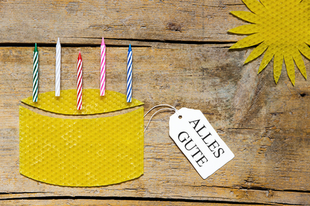 beeswax candle: beeswax, cake with candles and sun on wooden table, german words alles gute, which means all the best