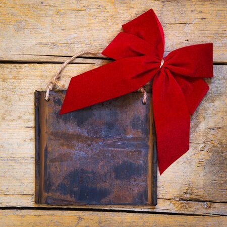 rusts: rusty metal sign on wooden table with a red ribbon, copyspace