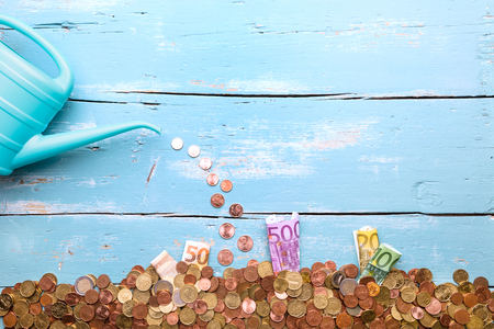Watering can with euro coins and banknotes on blue background, concept growing and plant