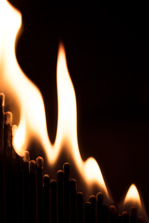 Concept business balance are burning down, matchsticks and fire, black background