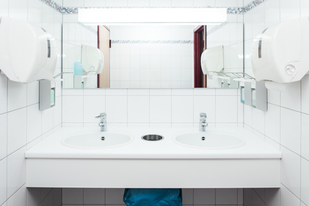 empty clinical white washing room with desinfecting agents Stock Photo
