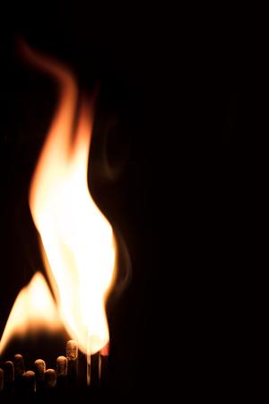 brandende lucifers en een grote vlam van vuur, zwarte achtergrond en copyspace Stockfoto