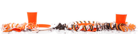 banner with halloween party decoration in orange and black, with paper plates and cups. in front of white background