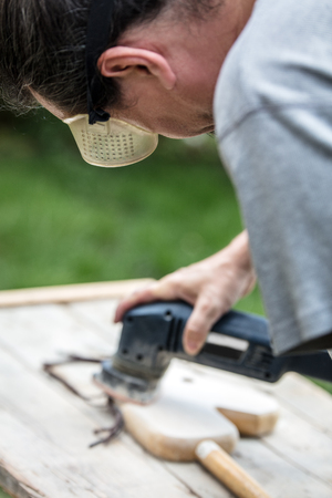 man is sanding an old hobbyhorse with an electric sander