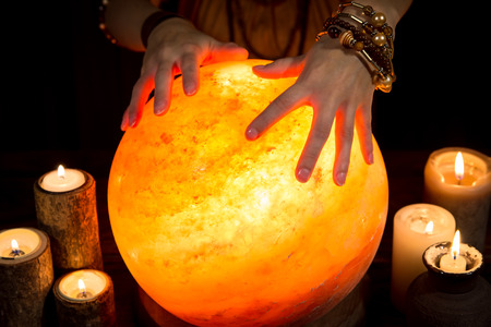 a shining crystal ball with candles and hands of a female fortune teller Stock Photo
