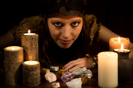 female Oracle with healing stones and Candles, concept Strenght and Love