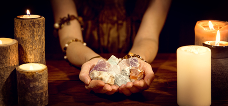 female fortune teller holding healing stones, concept esoteric and life coaching