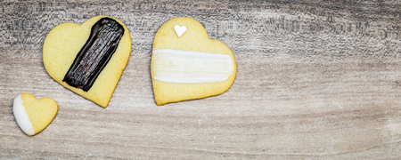 Three heart cookies, decoration with black and white glazing, banner with copyspace Standard-Bild