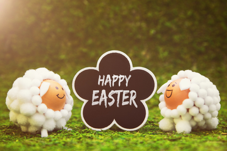 funny lamb figures and flower shaped slate with english text happy easter, green background with sunshine