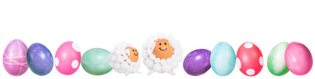 Banner, colorful dyed easter eggs and two funny lamb shaped eggs in a line, isolated on white Stock Photo