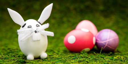 header, funny easter bunny figure and colorful dyed eggs on green moos Banque d'images