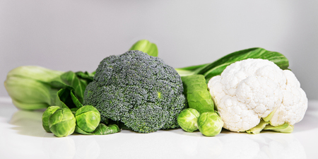 various vegetables in front of a white and grey background