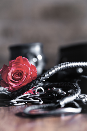 red rose with leatherwhip and handcuffs on a wooden table Archivio Fotografico