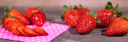 Panorama, fresh Strawberries intact and sliced on wooden table