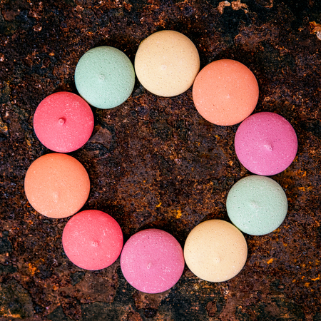 Topview, sweet delicious and colorful cookies or biscuits on rusty background, candy circle