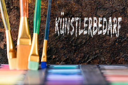 Brushes and colors, german word on rusty background, it means artist shop