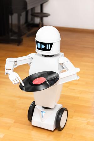 muziekrobot speelt een plaat af terwijl hij met zijn vinger de plaat aanraakt. Cocept muziek streamen of downloaden, futuristische muziekspeler