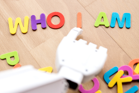 robot arm is pointing with his finger to colorful letters, building the sentence who i am