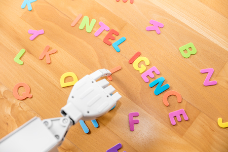 robot is pointing with his finger to the word intelligence Stock Photo