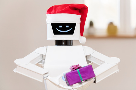 Ambient Assisted Living or aal robot with red xmas cap on his head, is holding a gift in his hands. portrait of a white service robot