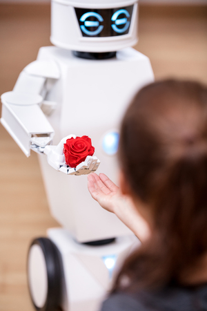 white cute service robot is giving a red rose to a pretty girl