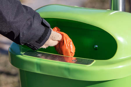 Woman putting a excrement bag from a dog into a waste bin containter, defecation of dog dirt